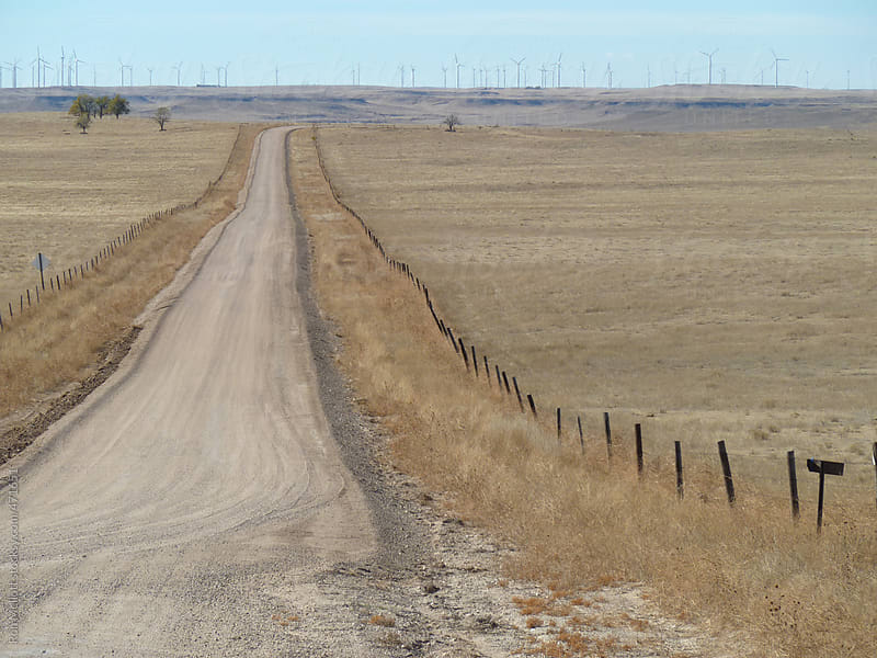 dirt gravel country secondary road leading to wind generators in the distance prairies barbed wire by Ron Mellott for Stocksy United