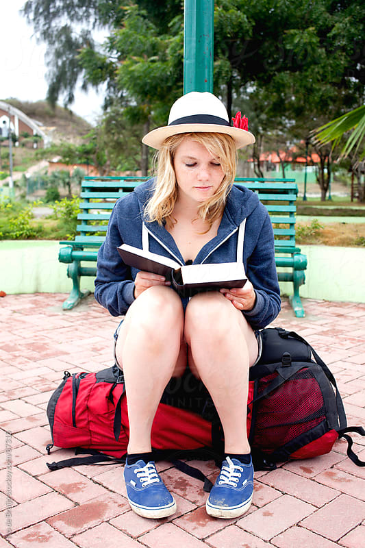 A young woman reading a book, sitting on a backpack, while traveling by Ivo de Bruijn for Stocksy United