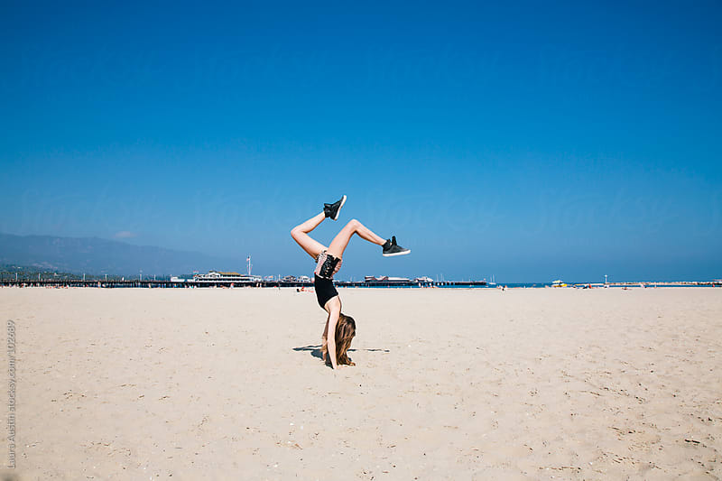 Girl Doing Handstand On The Beach by Laura Austin for Stocksy United