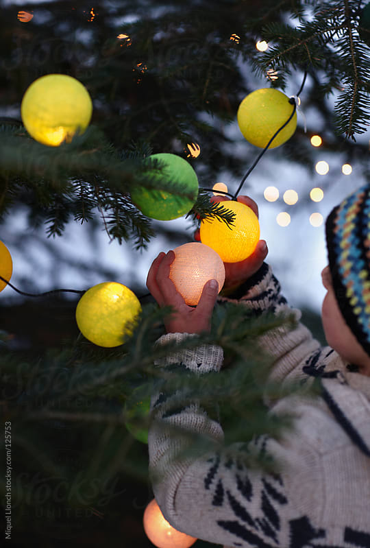 Child and christmas tree with ball lights and ornaments by Miquel Llonch for Stocksy United