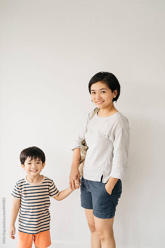 Mom and son smiling, looking at camera by Alita Ong for Stocksy United