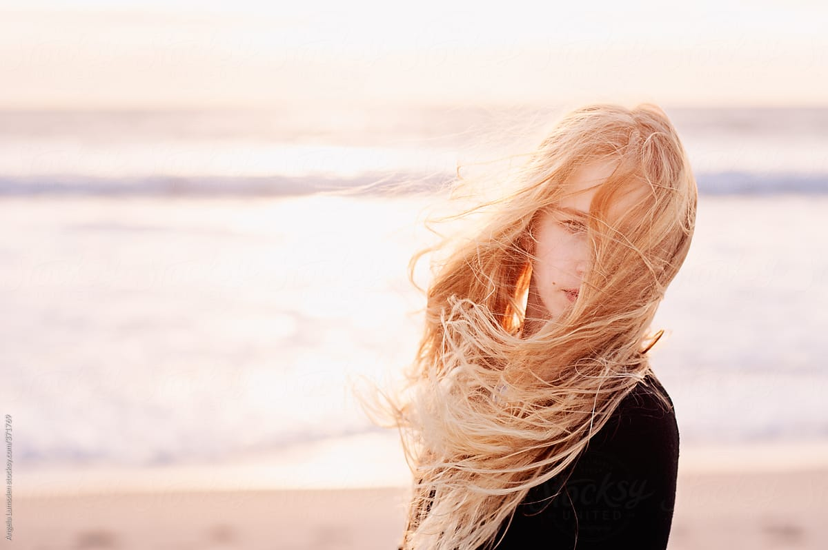 Pre Teenage Girl With Very Windswept Long Blonde Hair At The Beach In Winter By Angela Lumsden Stocksy United