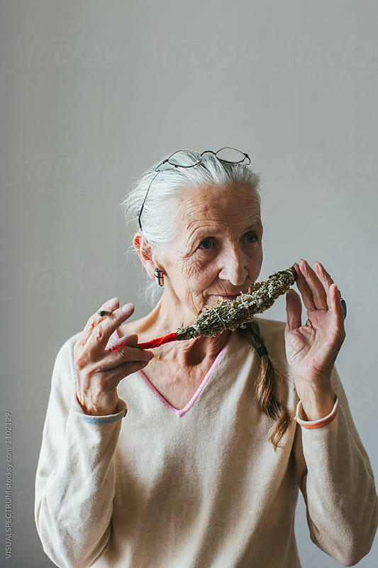 Indoor Portrait of Senior Smoking Woman with Grey Hair Smelling  by Julien L. Balmer for Stocksy United