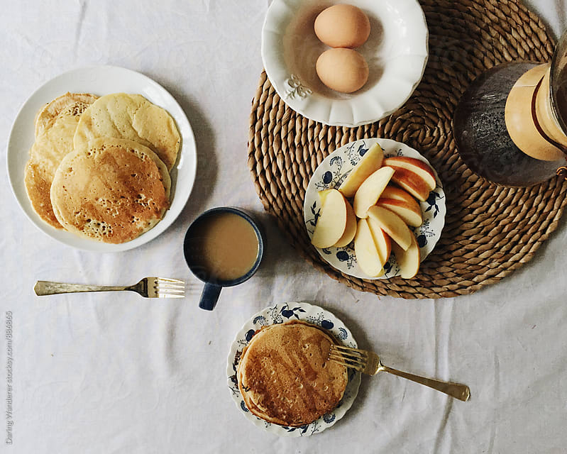 Healthy breakfast with pancakes, boiled eggs, coffee and apple slices by Daring Wanderer for Stocksy United