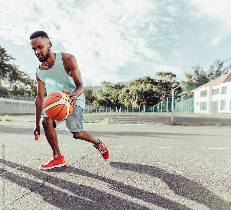 Young african man playing basketball with friends by Jacob Lund for Stocksy United