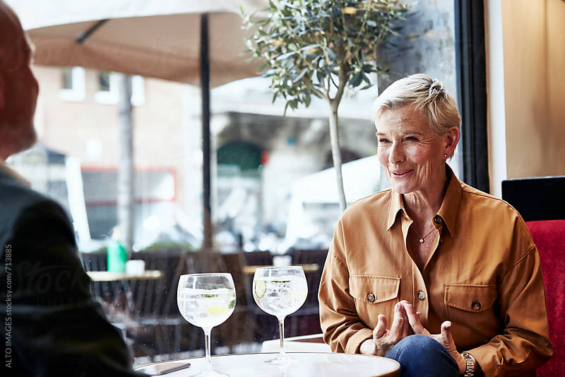 Senior Woman Talking With Man In Restaurant by ALTO IMAGES for Stocksy United