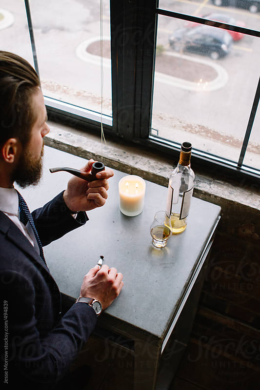 young man stands at window smoking pip and drinking whiskey by Jesse Morrow for Stocksy United