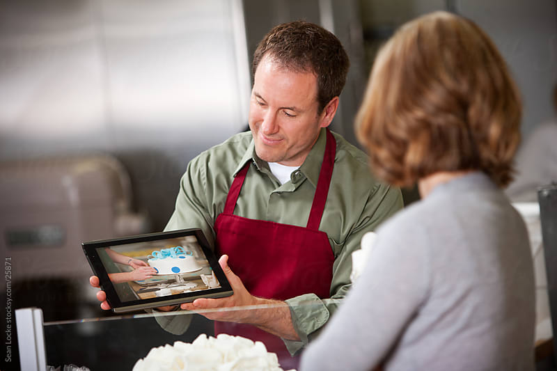 Bakery: Man Shows Cake Sample to Woman on Digital Tablet by Sean Locke for Stocksy United
