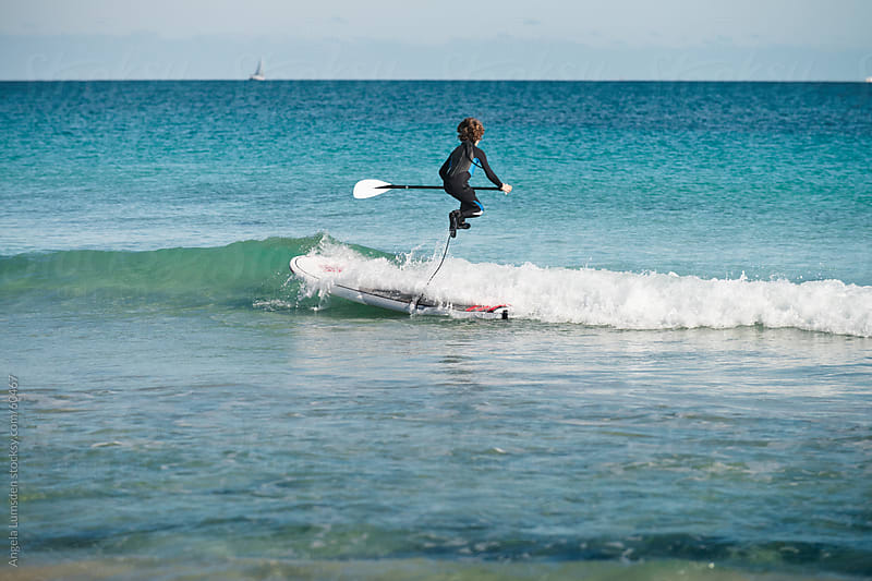 Boy jumps over a wave while paddle boarding by Angela Lumsden for Stocksy United