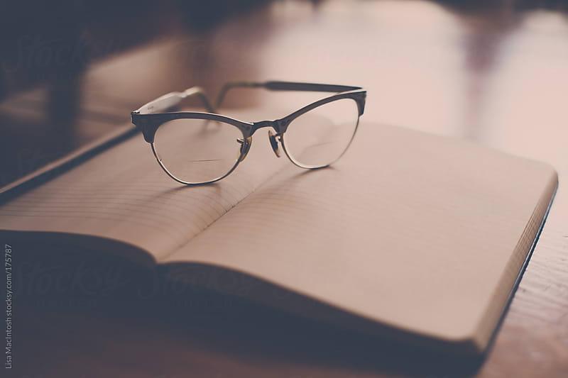 vintage glasses resting on book by Lisa MacIntosh for Stocksy United