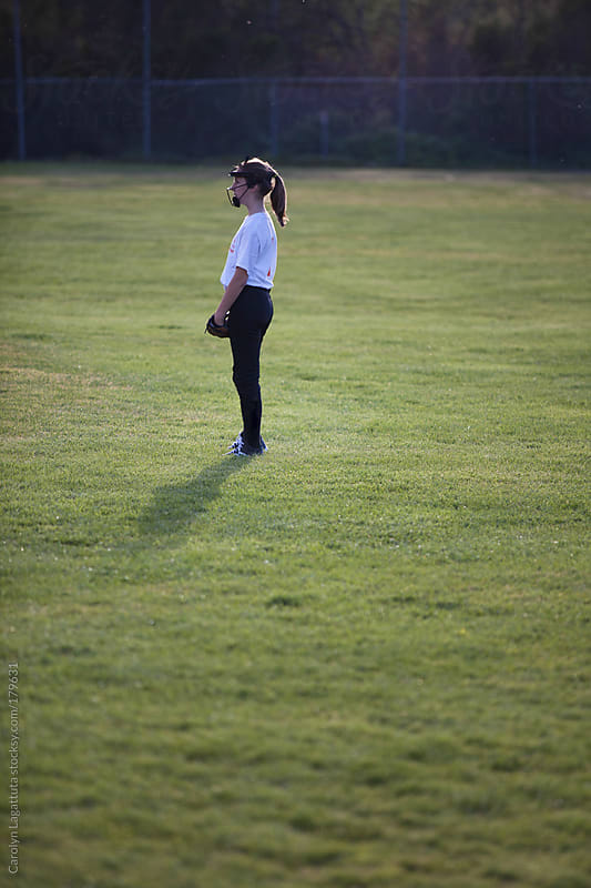 Young girl standing in the outfield at a softball game by Carolyn Lagattuta for Stocksy United