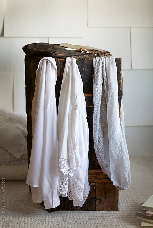 White hanging shirts on an old wood trunk in white paper room by Sherry Heck for Stocksy United