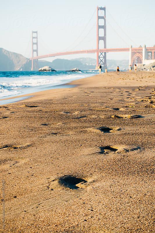 Footsteps In Sand Along Baker Beach With Golden Gate Bridge In Background by Luke Mattson for Stocksy United