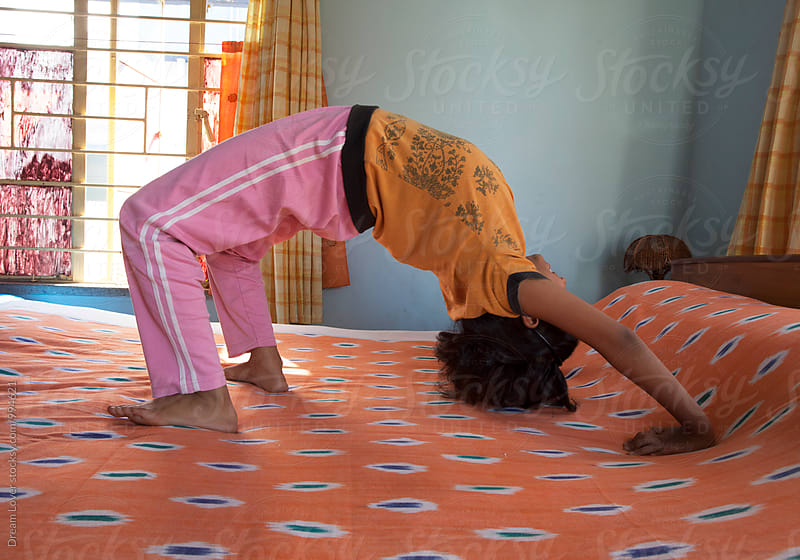 A little girl doing some Yoga poses inside house by PARTHA PAL for Stocksy United