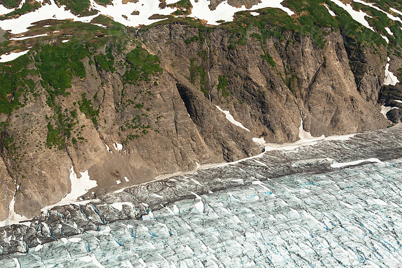 An Aerial Perspective of an Edge of a Glacier meeting a Mountainous Hillside by Willie Dalton for Stocksy United