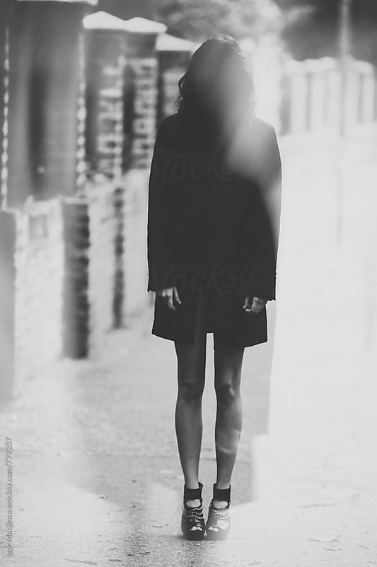 fashionable young woman dressed in a black coat on the street.double exposure by Igor Madjinca for Stocksy United