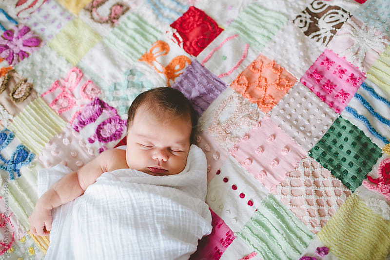 baby girl on quilt by Erin Drago for Stocksy United