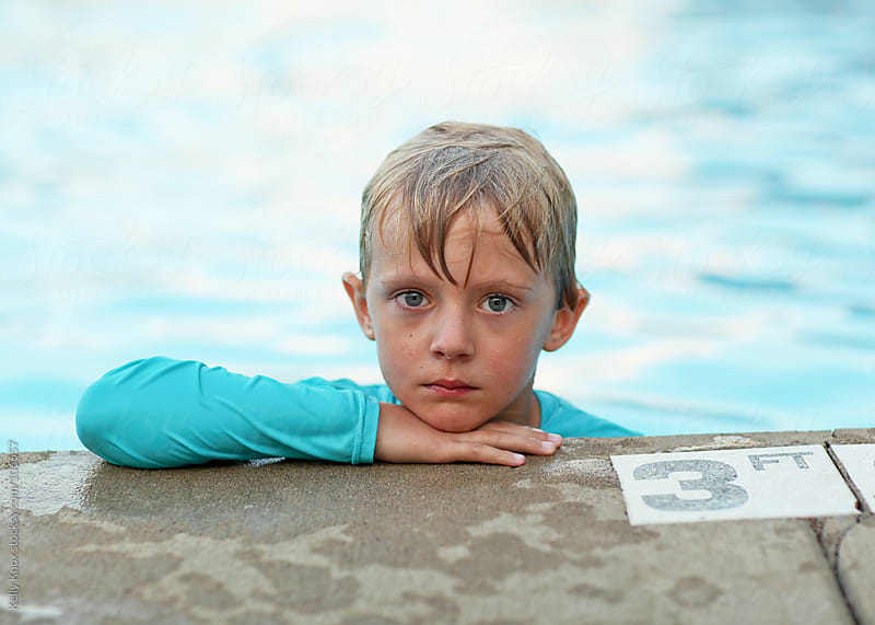 boy looking over the edge of a swimming pool by Kelly Knox for Stocksy United