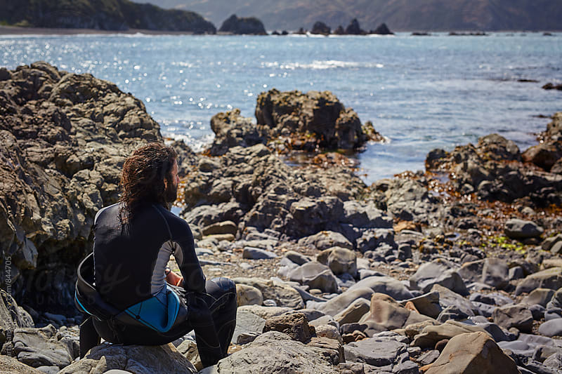 Young bearded diver sitting on rocky coastline by Martí Sans for Stocksy United