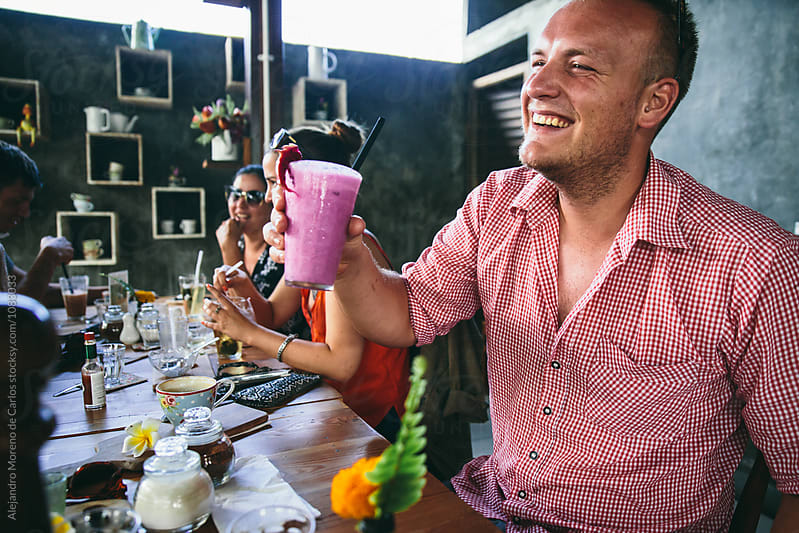 Happy man with healthy fresh drink in cafe with friends by Alejandro Moreno de Carlos for Stocksy United