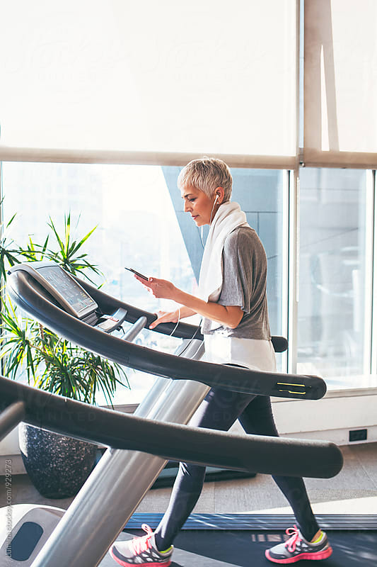 Senior Woman Listening to Music While Jogging by Lumina for Stocksy United