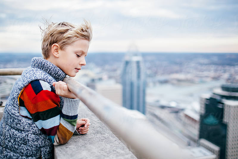 boy looks down at the city from the top of a building by Kelly Knox for Stocksy United