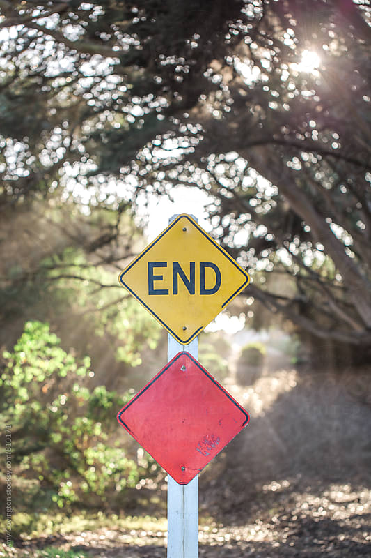 End sign at the end of a sunlit road by Amy Covington for Stocksy United