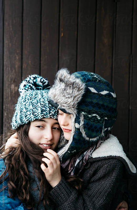 Sibling hug in the Winter in Winter clothes, in front of a wooden wall by Beatrix Boros for Stocksy United