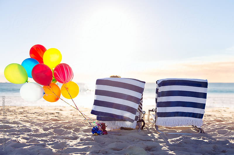 Two beach chairs and a bunch of balloons at the beach at sunset by Angela Lumsden for Stocksy United