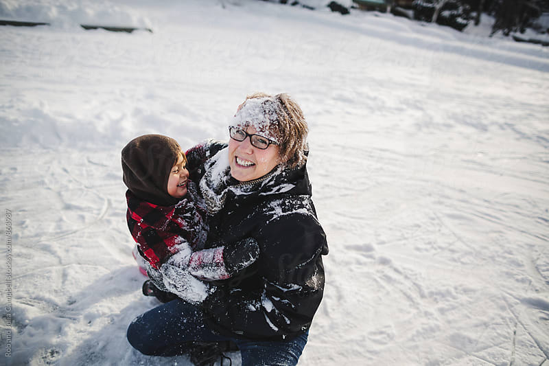 Energetic grandma playing with happy grandson in winter snow by Rob and Julia Campbell for Stocksy United