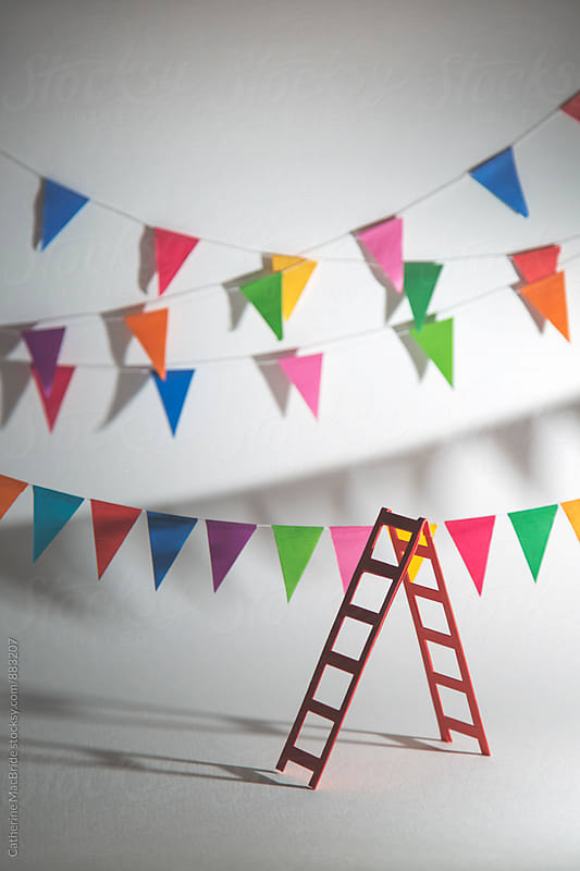 Hanging bunting in preparation for a party (vertical) by Catherine MacBride for Stocksy United