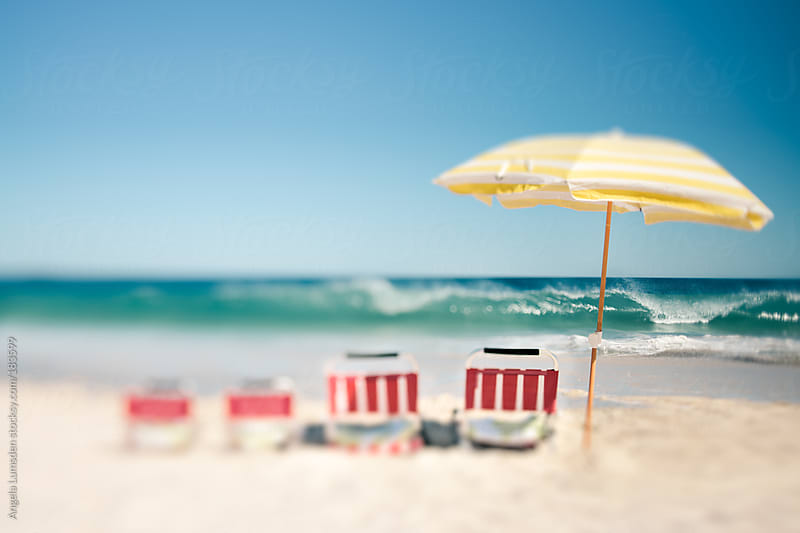 Beach chairs and sun umbrella in a row at the beach by Angela Lumsden for Stocksy United