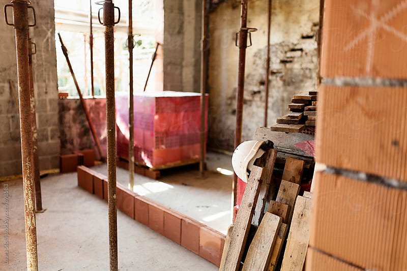 Working helmet and wooden boards inside house under construction by Laura Stolfi for Stocksy United