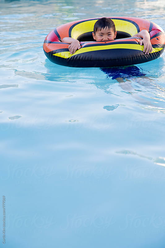 Young boy riding inner tube in pool by Curtis Kim for Stocksy United