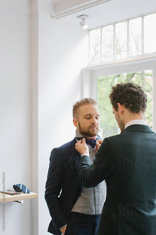 Men's Fashion - Man Helping Friend to Tie Bow Tie by Julien L. Balmer for Stocksy United