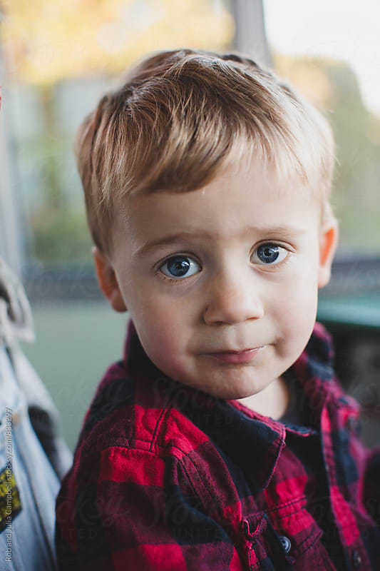Cute toddler boy in plaid shirt with big eyes looking at camera by Rob and Julia Campbell for Stocksy United