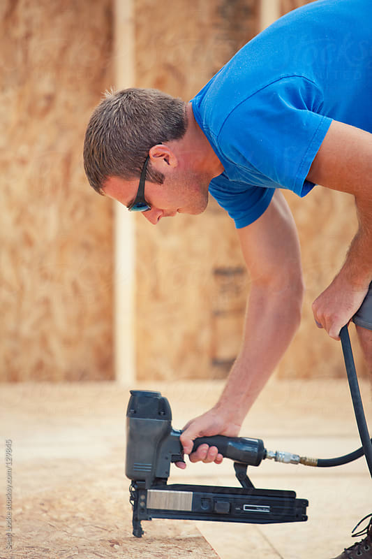 Construction: Worker Using Nail Gun to Do Construction by Sean Locke for Stocksy United