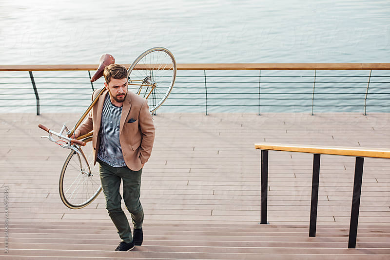 Businessman With a Bike by the River by Lumina for Stocksy United