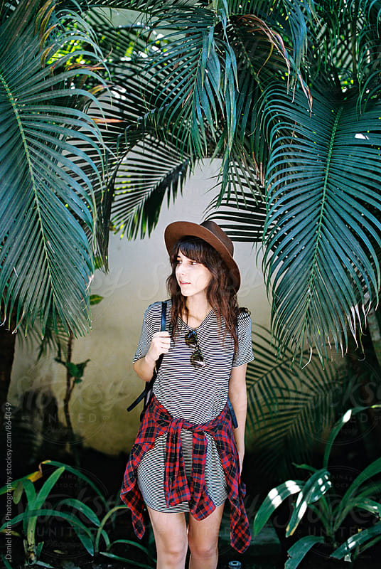 Young woman standing in front of palm fronds by Daniel Kim Photography for Stocksy United