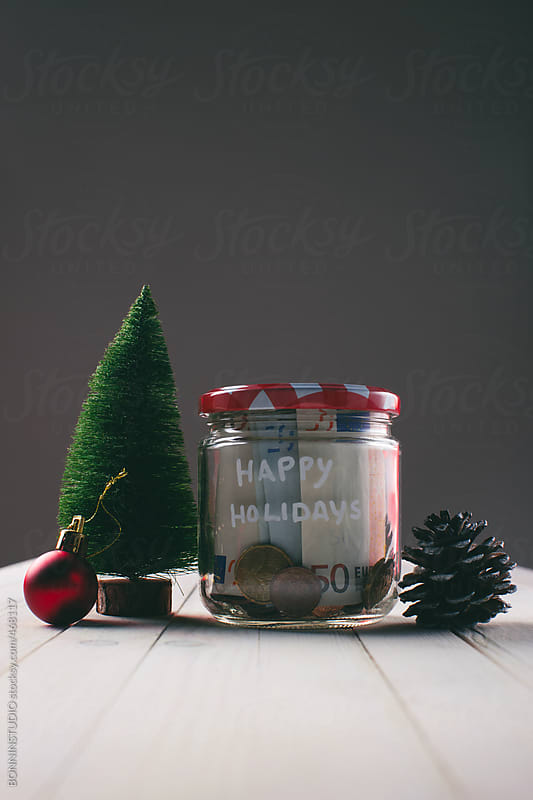 Saving money for Christmas in a jar.  by BONNINSTUDIO for Stocksy United