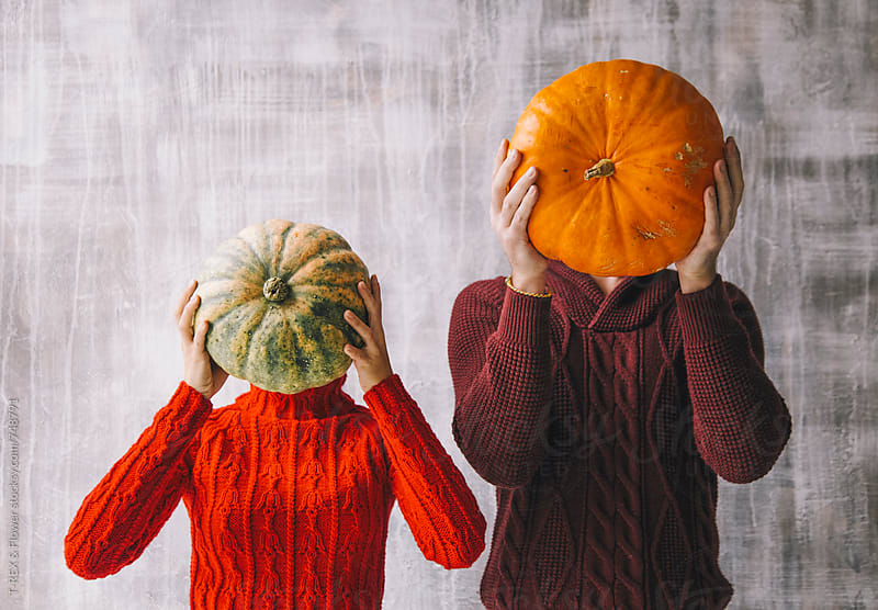 Couple holding pumpkins in front of faces by T-REX & Flower for Stocksy United