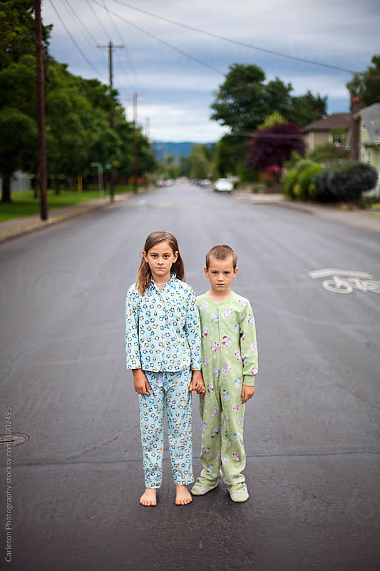Pajama wearing children standing in the street by Carleton Photography for Stocksy United