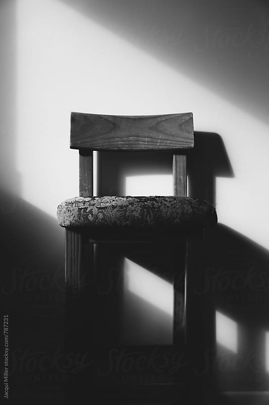 Black and white of old chair in harsh directional light by Jacqui Miller for Stocksy United