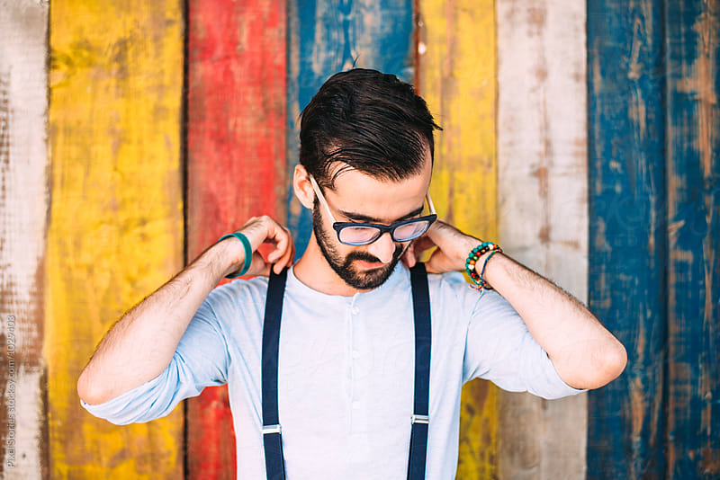 Young man fixing his suspenders against colorful wall by Pixel Stories for Stocksy United
