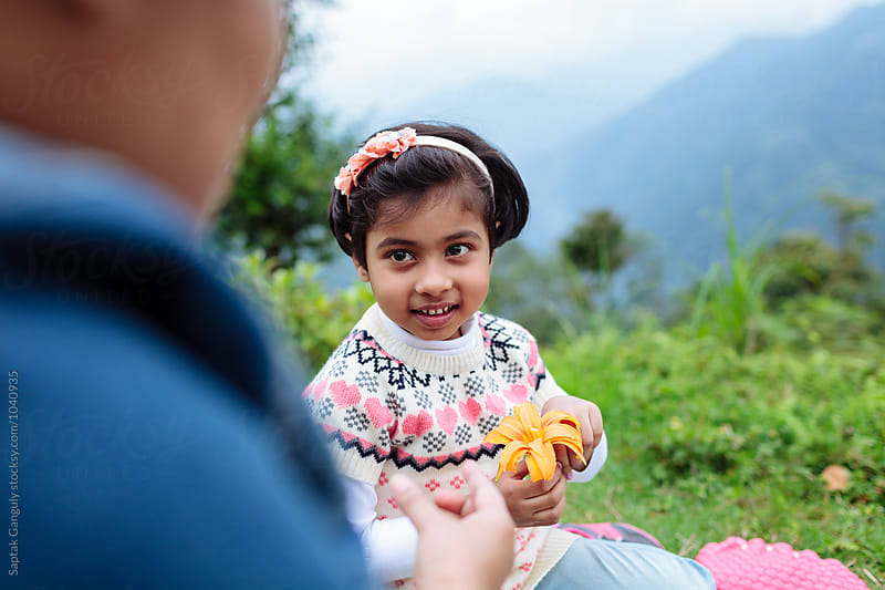 Cute little girl with flower smiling by Saptak Ganguly for Stocksy United