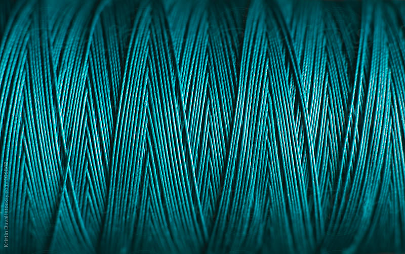 Close up spool of blue cotton thread by Kristin Duvall for Stocksy United