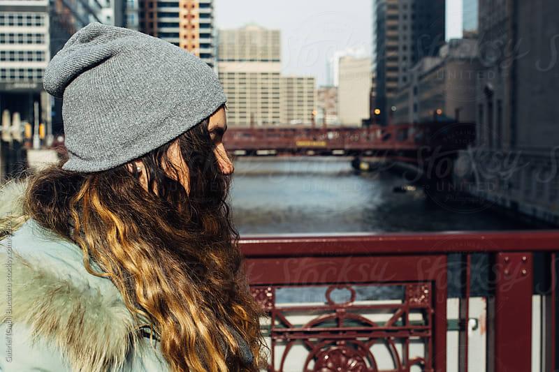 Teen girl walking on a bridge in a city by Gabriel (Gabi) Bucataru for Stocksy United