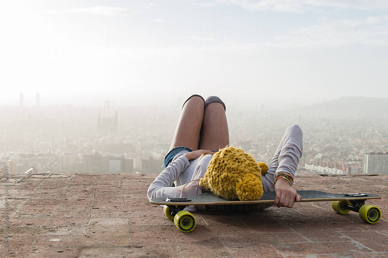 Relaxing person on skateboard against of Barcelona cityscape by Guille Faingold for Stocksy United