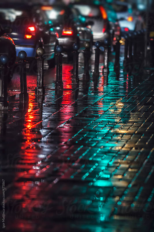 street atmosphere, rain, cars,green  red reflections, vertical  by Igor Madjinca for Stocksy United