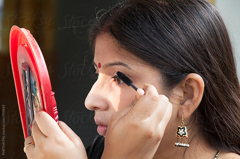 Indian woman applying MASKARA in eye for beautification by PARTHA PAL for Stocksy United